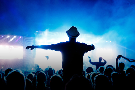 Silhouette Concert Person, Man on Shoulders in Crowd with hands up at a Music Festival - Backlit with Lighting.