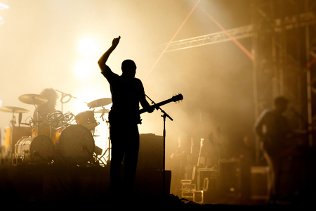 Groupes de silhouettes sur un concer, chanteur avec guitare, main levée Banque d'images - 88153797