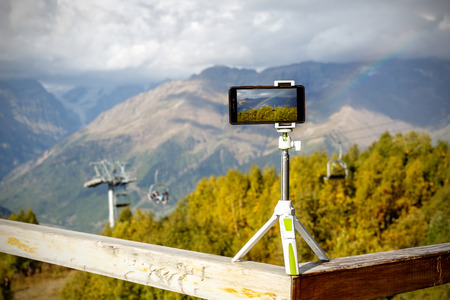 smartphone on a tripod in the mountains, a lift and a rainbow on the background