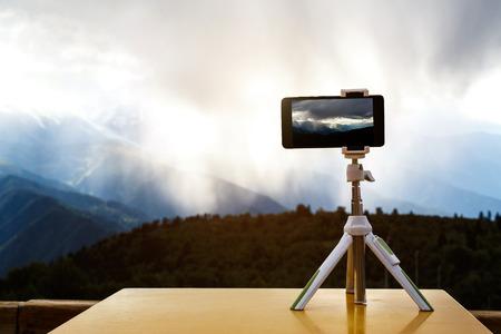 smartfon na statywie w górach, burza na tle
