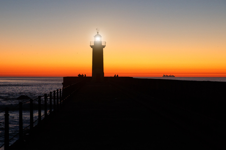 Lighthouse on the ocean, silhouette at sunset
