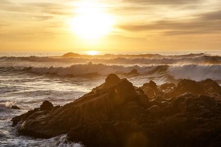 Sea waves crashing onto the rocks on sunset, Pacific Coast