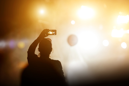 Silhouette of girl with a smartphone taking photo of concert stage