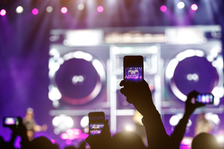 Silhouette of a hand with a smartphone at a concert, record show on the stage