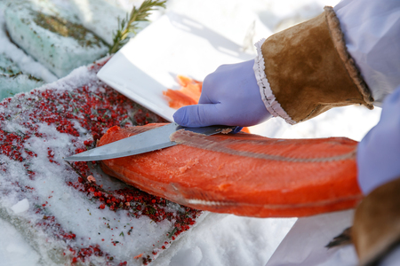 Cutting frozen fish, salmon, on fillets. Red kitchen board, hands in special blue gloves.