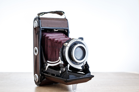 Old vintage camera on table, white background Stock Photo