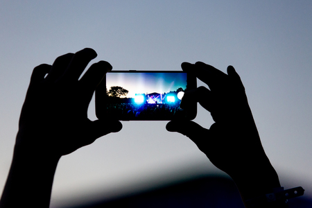 silhouette of hands with a smartphone at a big music festival, video recording
