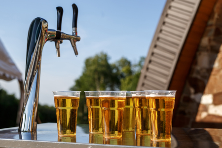 A row of plastic beer glasses with a lager beer on outdoor party