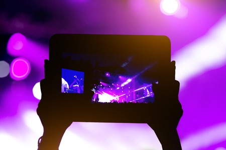 Recording a concert, silhouette of hands with tablet