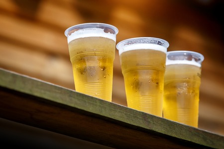 A row of plastic beer glasses with a beer on a party, cold beer Stock Photo