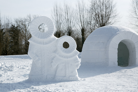 Ice sculpture of a family of northern people near round icehouse , Snowhouse hurt