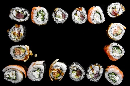Sushi rolls with salmon, tuna, cucumber and green onions on black background, with reflection