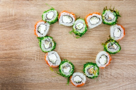 Sushi rolls lay on the table in the shape of a heart. Holiday set for St. Valentines Day. Top view.
