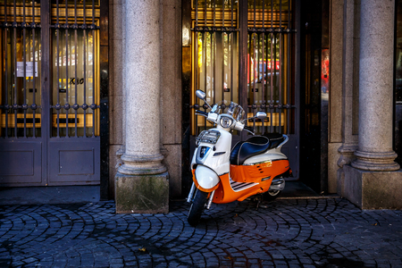 Retro red scooter on the street in a European city.