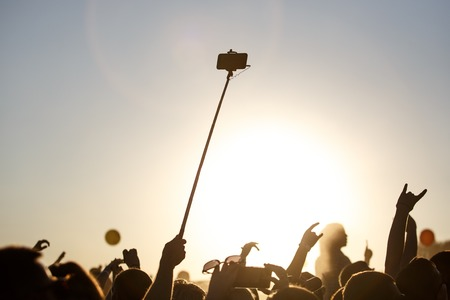 A smartphone on a self-stick, a summer music festival at sunset.