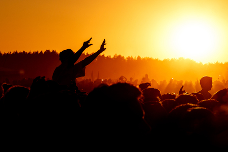 Man with raised hands cheering at outdoor music, rock festival