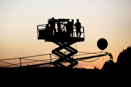 Silhouette of group of cameramen on the lift at a summer event, concert