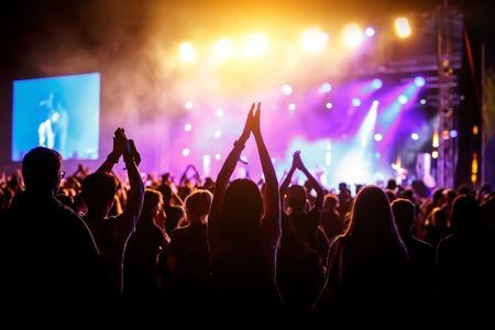 handen van gelukkige mensen die plezier hebben op het podium van het live rockfestival in de zomer