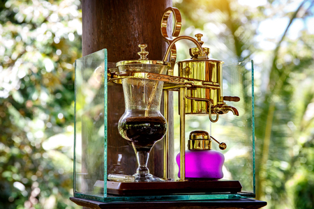 Making legendary coffee, Kopi Luwak, in a vintage siphon. Bali, Indonesia