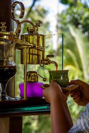 Making legendary coffee, Kopi Luwak, in a vintage siphon. Bali, Indonesia