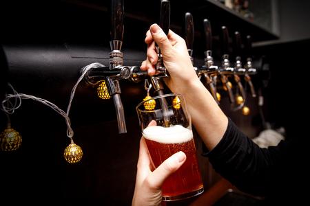 Il barista versa la birra fresca dal rubinetto nel rubinetto.