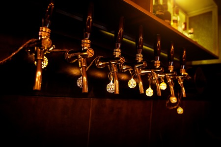 Row of beer taps in craft bar