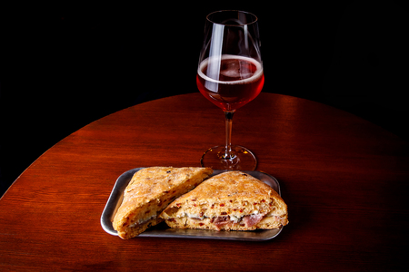 A glass of beer and a sandwich in a bar on a wooden table. Stockfoto