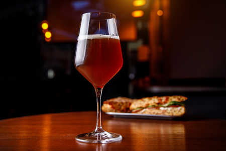 A glass of beer and a sandwich in a bar on a wooden table.