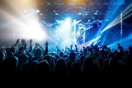 Muchas manos, multitud en concierto, luz azul. Foto de archivo