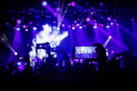 Smartphone in mano a un concerto, luce blu dal palco. Archivio Fotografico