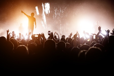 Rock concert. Leader on the stage. Silhouette of the crowd in front of the stage