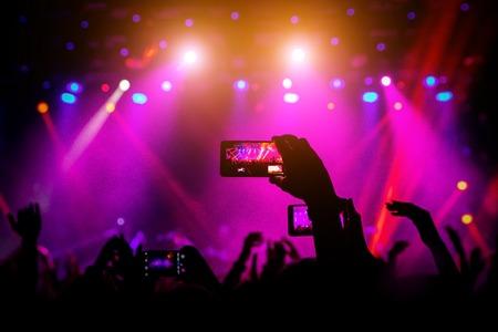 Smartphone en mano en un concierto, luz roja del escenario