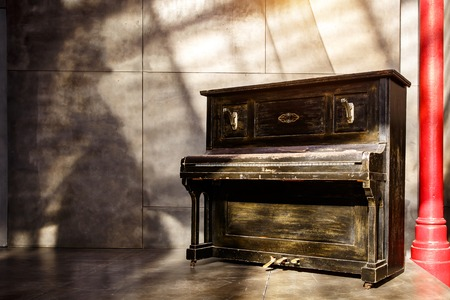 Old shabby black piano near the wall. Sunset light, shadows on the wall