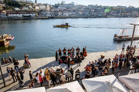 Porto, Portugal - November 13, 2018: Musical group on the embankment of Porto, Portugal. Listeners around.