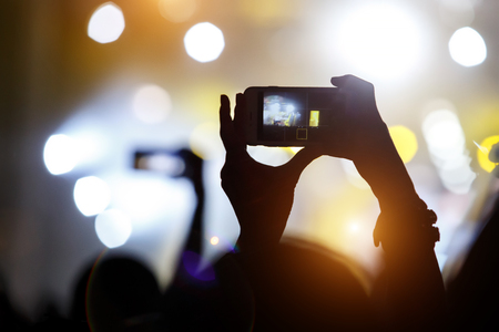 A mobile phone in the hands of fan at summer music show. Recording concert Banco de Imagens