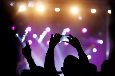 A mobile phone in the hands of fan at summer music show. Recording concert Imagens
