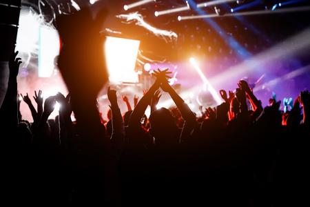 Menschen mit erhobenen Händen bei einem Konzert ihrer Lieblingsgruppe. Menschenmenge, die eine Show sieht