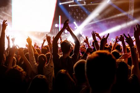 Persone con le mani alzate a un concerto del loro gruppo preferito. Folla che guarda uno spettacolo