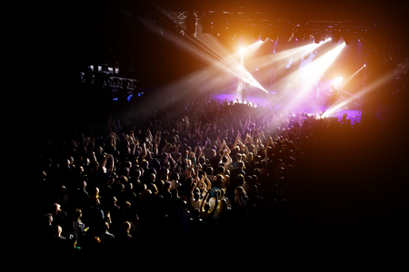 People with their hands up at a concert of their favorite group. Crowd watching a show