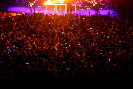 People with their hands up and smartphones at a concert of their favorite group. Crowd watching a show