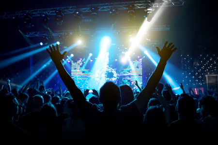 Silhouette of man with raised hands on music concert.