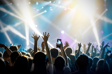 Raised hands in honor of a musical show on stage, People in the hall Imagens