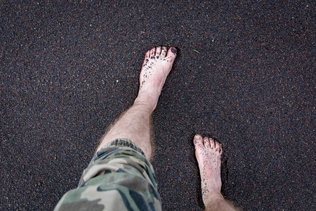 Mens feet are on the volcanic black sand.