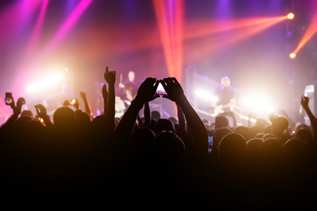 Crowd with raised hands and smartphone record a concert