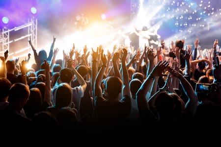 Multitud con las manos levantadas en concierto de música. Foto de archivo