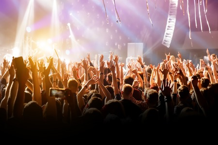 A man with his hands up at a concert of his favorite group. Light from the stage