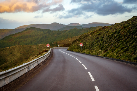 Empty road in the mountains. Sunset. No overtaking sign