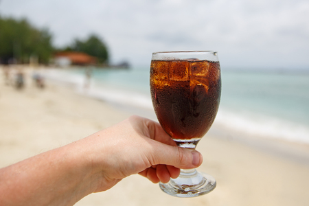 Cooling drink in hand on beach.