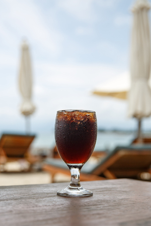 Cola glass on beach with umbrellas. Cooling drink on summer. Reklamní fotografie