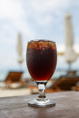 Tulip glass with cola on table. Beach umbrellas on the background Reklamní fotografie